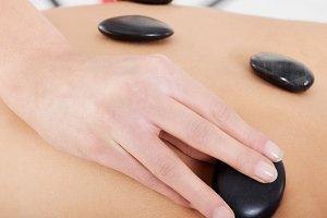 Close up on female's back having stone massage.