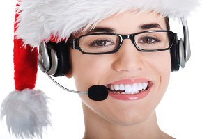 Portrait of woman in santa hat with microphone and headphone.