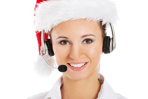 Young business woman in santa hat, microphone and headphones.