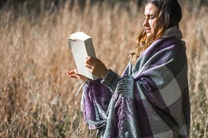 young girl on a field reading a book
