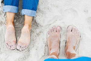 Female and male feet on the beach