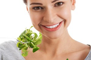 Young casual woman eating lamb's lettuce.