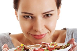 Beautiful young woman with cookies on a plate.