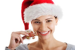 Young beautiful woman in santa hat and a cookie.