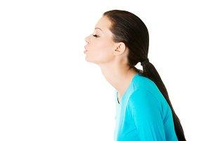 beautiful casual woman sending a kiss.
