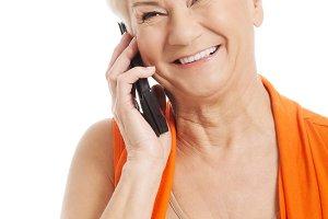 An old woman talking through phone.