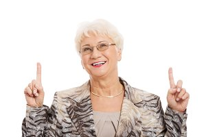 An old casual lady pointing up on copy space.