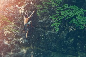 Free climber man climbing on stone rock outdoor in summer, bouldering