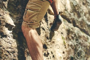 Adult Male Mountaineer In sports equipment climbs a rocky wall. Unrecognizable adult man in shorts, legs and shoes for excitation