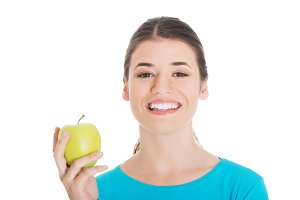 Beautiful casual woman holding an apple.