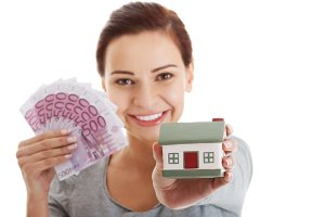 Beautiful young, casual woman holding money and house.