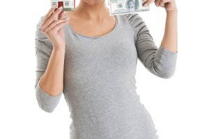 Beautiful casual woman holding money and house.