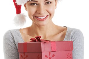 Beautifull woman in santa hat holding presents.