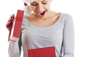Beautiful woman in santa hat and opening present.
