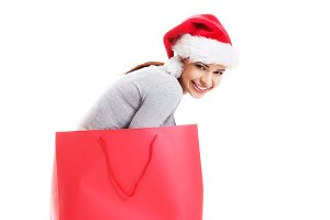 Beautiful girl wearing santa hat in red shopping bag.