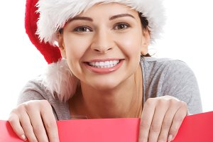 Beautiful woman wearing santa hat, holding shopping bag.