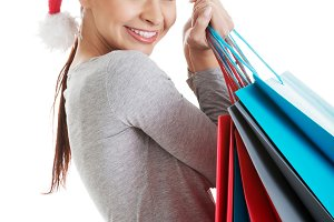 Beautiful woman in santa hat carrying shopping bags.