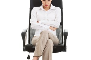 Young sad business woman sitting on a chair.