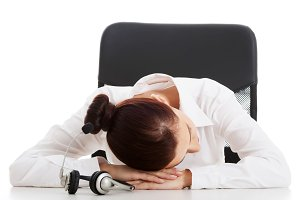 Young beautiful business woman on call center is sleeping on table.