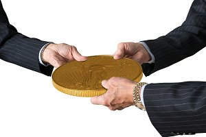 Isolated three traders hands holding large gold coin