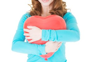 Attractive casual woman holding a baloon heart.