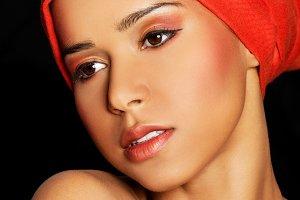Attractive woman's face in turban. Closeup.