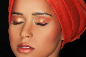 Attractive woman in turban with closed eyes. Closeup.
