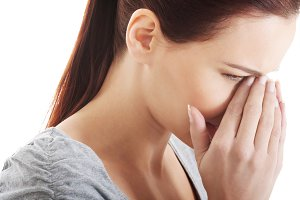 Beautiful woman touching her nose.