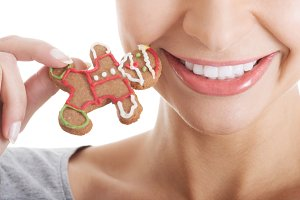 Beautiful woman eating gingerbread cookies.