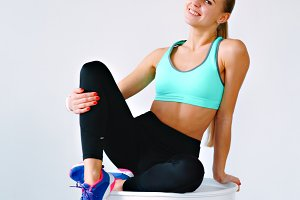Fitness blonde girl sitting on a stretched white barrel gym