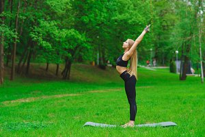 The girl in the park is engaged in gymnastics