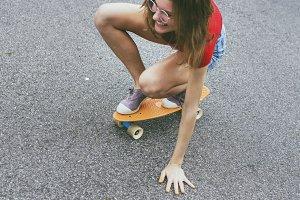 Hipster girl riding a skateboard