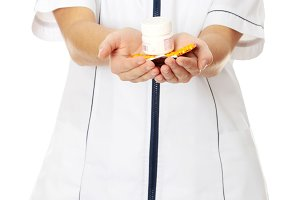 Young female nurse holding pills.