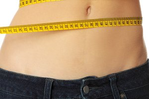 Slim woman's body with measuring tape.
