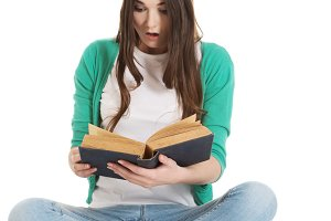 Young woman student sitting and reading a book.