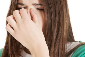 Young beautiful woman with sinus pressure, touching her nose.