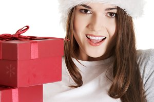 Young beautiful woman in santa hat with presents.