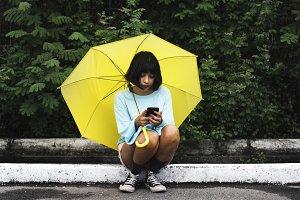 Girl using phone under umbrella