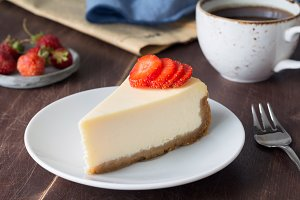Cheesecake with strawberries and cup of coffee