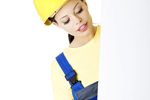 Beautiful young worker woman in protective clothes.