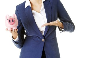 Young business woman holding piggy- bank.