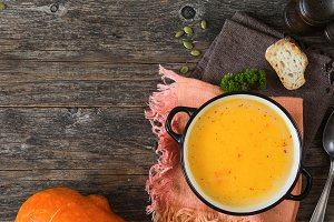 Pumpkin cream soup bowl on wooden background