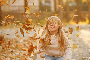 Little girl throws fallen leaves.