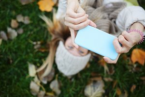 Girl doing selfie lying on leaves.