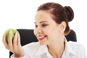 Young beautiful business woman holding an apple.