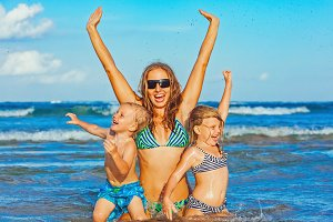 Happy mother with kids on the beach