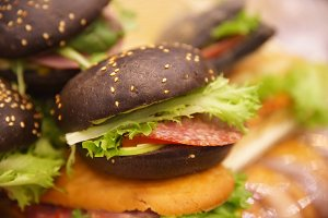Black burger with tomato and salad