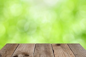 Wooden table with green nature bokeh