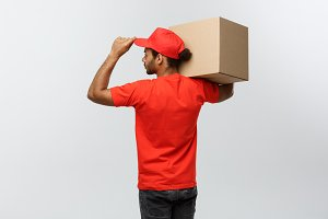 Delivery Concept - back view of Handsome African American delivery man with box package. Isolated on Grey studio Background. Copy Space.