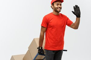 Delivery Concept - Portrait of Handsome African American delivery man or courier pushing hand truck with stack of boxes. Isolated on Grey studio Background. Copy Space.